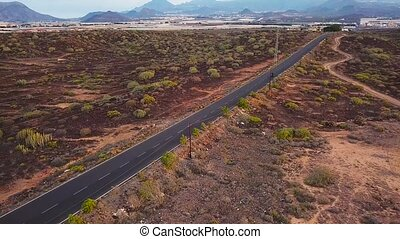 Aerial view of motorcyclist traveling up a desert road -...