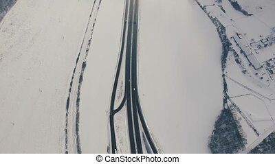 Aerial view of motorway in winter. Cars driving on a...