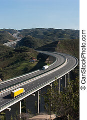 Aerial view of motorway with yellow and white trucks