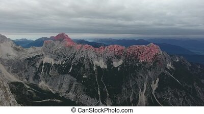 Aerial view of mountain ridge at dawn. Ponce and Mangart illuminated by pink light.