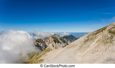Aerial view of mountain ridge surrounded with clouds. Stol...
