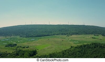 Aerial view of multiple wind generators above the forest. Green energy production concept