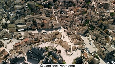 Aerial view of narrow streets of ancient city of Matera above roofs of houses