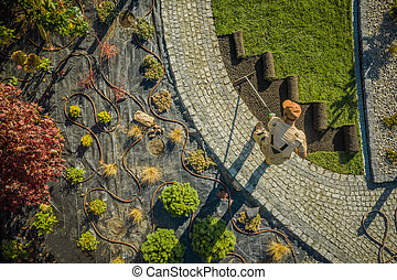 New Residential Garden Developing by Caucasian Landscaping Worker