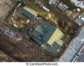 Aerial view of new residential house cottage and garage or barn with shingle roof on fenced yard on sunny day.