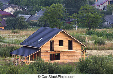 Aerial view of new wooden ecological traditional house cottage of natural lumber materials with attic floor, porch, balcony and shingle roof under construction in rural area.