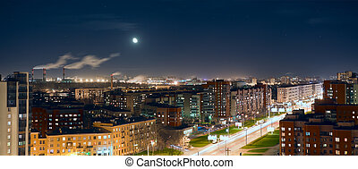 Aerial view of night city with lights and moon