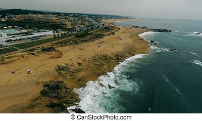 Aerial view of ocean Portugal waves crashing on beach, drone footage.