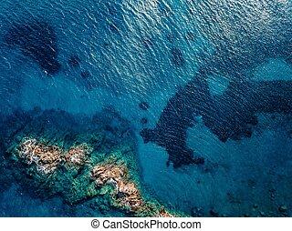Aerial view of ocean waves and rocks.