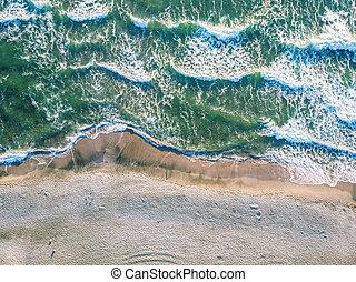 Aerial view of ocean waves crashing on beach.