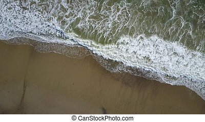 Aerial view of ocean waves crashing on beach with people walking by, 4K drone footage