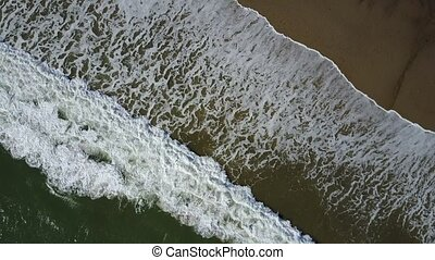 Aerial view of ocean waves crashing on beach with people walking by, drone footage