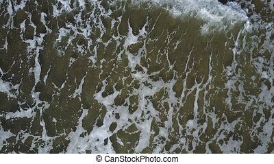 Aerial view of ocean waves crashing on beach with people walking by,