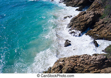 Aerial view of ocean's beautiful waves and rocky coast