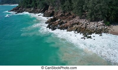 Aerial view of ocean's beautiful waves and rocky coast with greenery