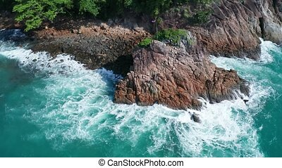 Aerial view of ocean's beautiful waves and rocky tropical coast with Thai flag on the rock's peak