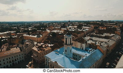 Aerial view of old city center with old houses and town hall. Drone flies over the roofs