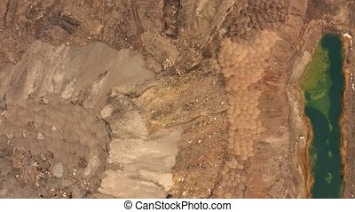 Aerial view of opencast mining quarry with lots of machinery at work - view from above. Slag pit