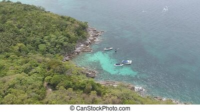 Aerial view of palm trees and sea with boats - Aerial drone...