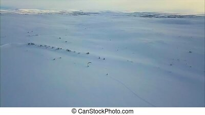 Aerial view of people snowkiting in tundra. filmed with...
