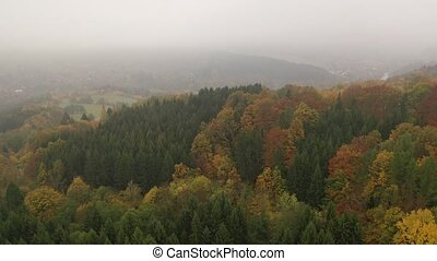 Scenic autumn country landscape with colorful trees on hillsides and empty fields