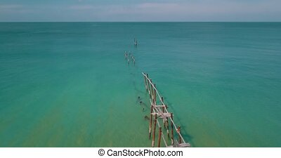 Aerial view of piles stick out in the water of the sea -...