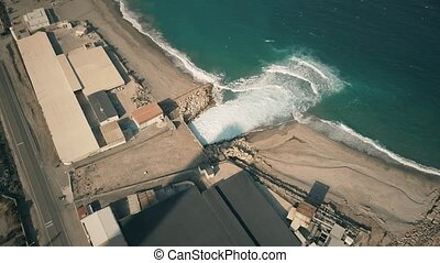 Aerial view of polluting industrial water drain into sea -...