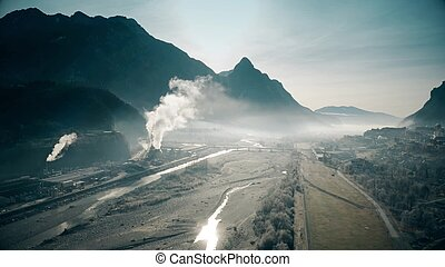 Aerial view of polluting plant in the river valley, northern Italy