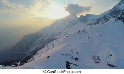 """Aerial view of popular ski resort in Alps, mountains covered with snow, cableway"""