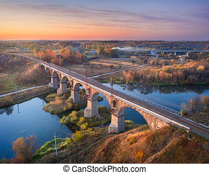 Aerial view of railroad bridge and river at sunset in autumn