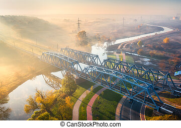 Aerial view of railroad bridge and river in fog at sunrise