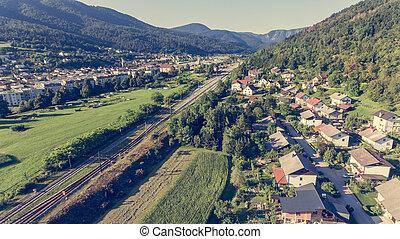 Aerial view of railroad running through a town.