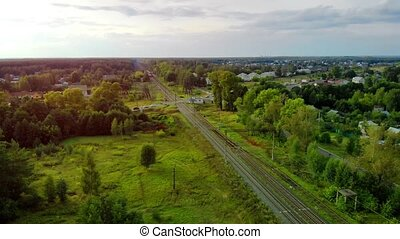 Long, straight stretch of railroad track, cutting through the flat terrain of a remote town in Russia, from an aerial perspective. Stock footage 4k