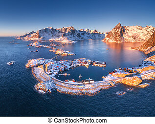 Aerial view of Reine and Hamnoy at sunset in winter. Amazing Lofoten islands, Norway. Panoramic landscape with blue sea, snowy mountains, rocks, village, buildings, rorbuer, road, bridge, sky. Top view