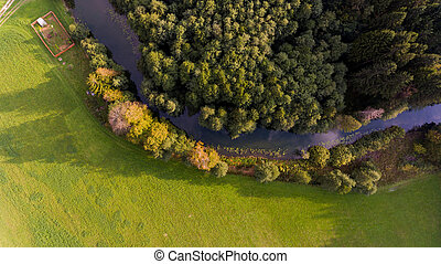 Aerial view of river bend through forest.