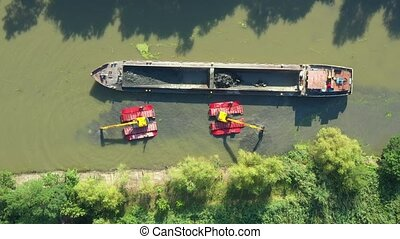 Aerial view on excavator dredge is dredging, working on river, canal, deepening and removing sediment, mud from riverbed in a polluted waterway.
