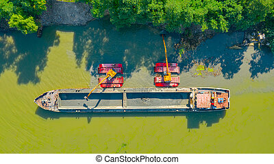 Aerial view of river, canal is being dredged by excavator