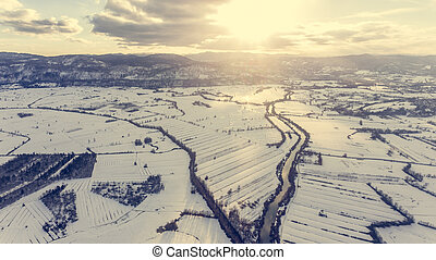Aerial view of river flowing through snow covered countryside at sunset.