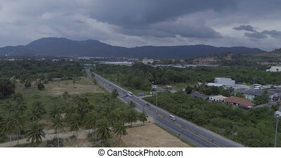 Aerial view of road and palm trees with mountains and sky ...