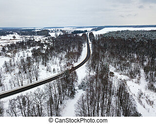 Aerial view of road bends in winter forest. Winter snowy landscape