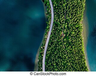 Aerial view of road between green forest and blue lake in Finland