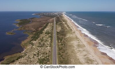 Aerial view of road between oceanside and soundside. 4k