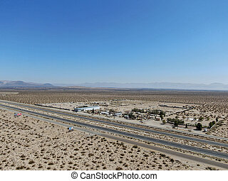 Aerial view of road in the middle of the desert under blue sky in California's Mojave desert, near Ridgecrest.