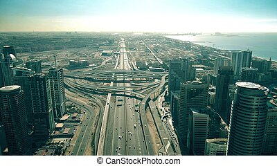 Aerial view of road traffic at big urban highway intersection and modern skyscrapers. Dubai, UAE