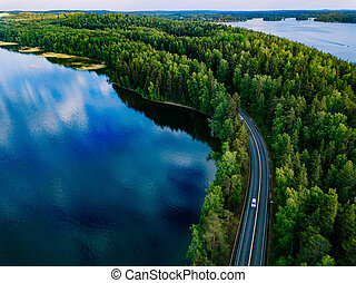 Aerial view of road with cars between green forest and blue lake water in Finland