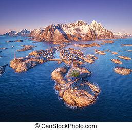 Aerial view of rocks in sea, snowy mountains, purple sky