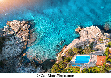 Aerial view of rocky beach, pool, green trees and blue sea