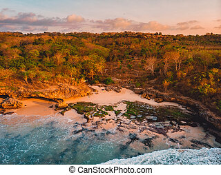 Aerial view of rocky coastline with beach, waves and warm light. Bali, Indonesia