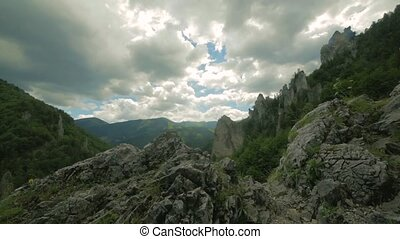 Aerial view of rocky hills with green coniferous trees