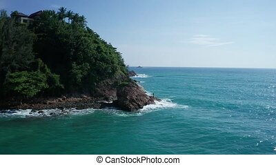 Aerial cinematic footage of rocky tropical island's coast with Thai flag and fisherman over beautiful sea and sky background
